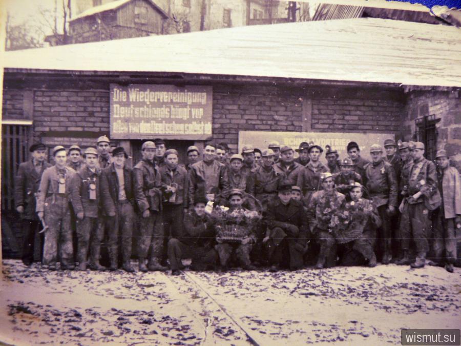 Mijnwerkers poseren voor een bord waarop 'De hereniging van Duitsland hangt vooal af van de Duitsers zelf. (Wismut.su)