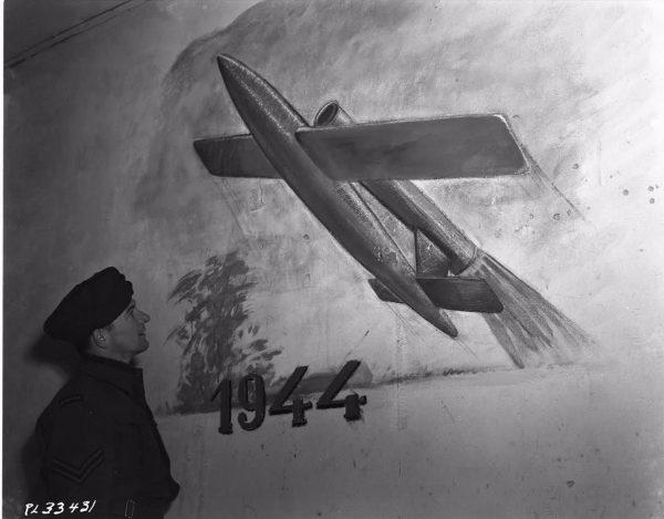 Geallieerde militair bekijkt een muurschildering van een V-1 collectie (collectie Canadian Forces Joint Imagery Centre)