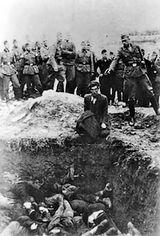 Duitse soldaten kijken toe hoe een lid van Einsatzgruppe D een Joodse man neerschiet bij een massagraf in Vinnitsa, Oekraïne (1942)