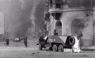 Een opname van de straatgevechten in Boedapest. Op de voorgrond een stukgeschoten Sovjet-pantserwagen.