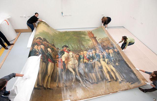 Het uitrollen van het schilderij – Foto: Amsterdam Museum