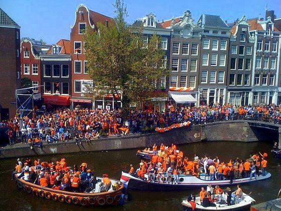 Op Koninginnedag kleuren de Amsterdamse grachten oranje