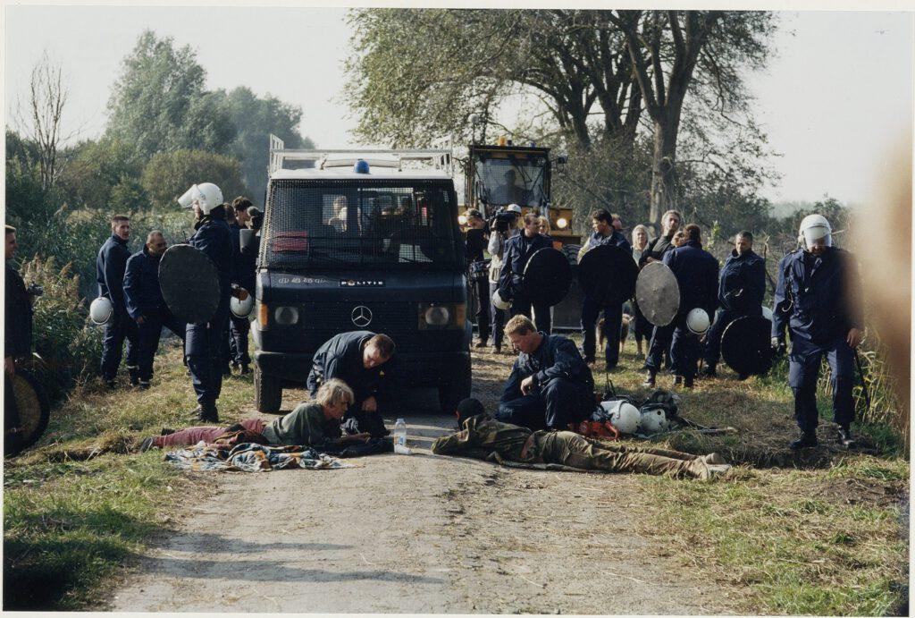 Actievoerders, met een arm vergrendeld in het wegdek, blokkeren de oprukkende Mobiele Eenheid tijdens de ontruiming van Ruigoord, 1997