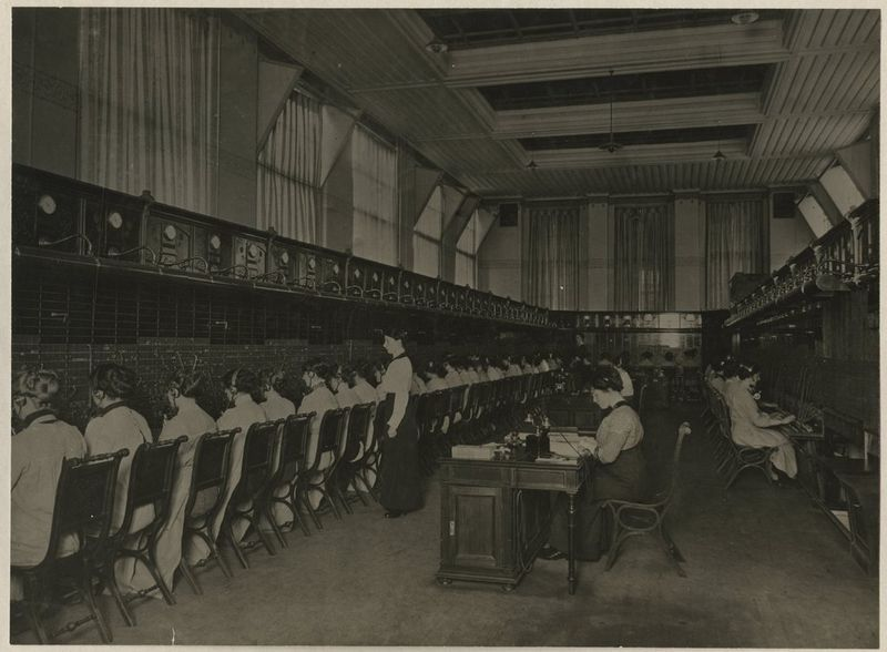 In 1903 richtte de gemeente een eigen telefoondienst op. Deze had in dat jaar 2032 abonnees. 10 Jaar later waren dat er al meer dan 9000. In de telefooncentrale werkten 122 telefonistes die de bellers doorverbonden met het gewenste nummer. - Telefooncentrale Hofstraat 2, telefoonzaal boven, foto gemaakt door onbekende fotograaf rond 1910 – Collectie Haags Gemeentearchief