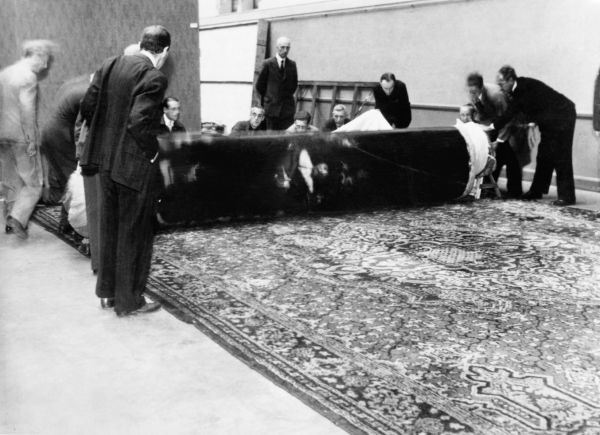 De Nachtwacht keert terug in het Rijksmuseum. Het doek wordt op 30 juni 1945 voorzichtig afgerold na enkele jaren opgerold bewaard te zijn geweest, op het laatst in een mergelgrot bij Maastricht. - Foto: U.S. National Archives