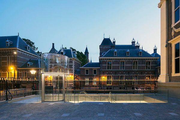 Glazen lift bij het Mauritshuis, met daarachter het Binnenhof (Hans van Heeswijk Architecten)