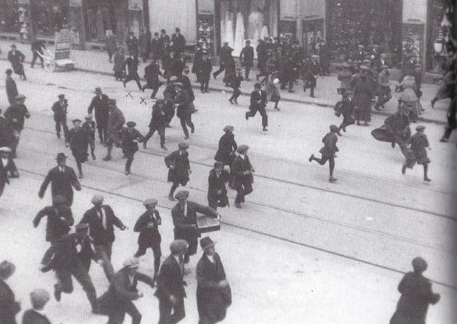 Tijdens een 'hongeroproer' in 1918 voeren twee agenten met gummiknuppels een charge uit op het Damrak in Amsterdam.