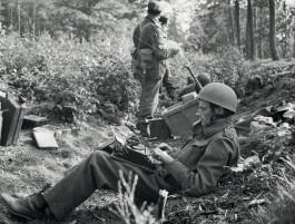 Alan Wood, een Britse journalist die bij Arnhem met de para's meegesprongen was, schrijft in een greppel aan de Utrechtseweg op 16 september 1944 zijn verslag voor de Daily Express - © uit: De bevrijding in Beeld  / Vantilt fragma