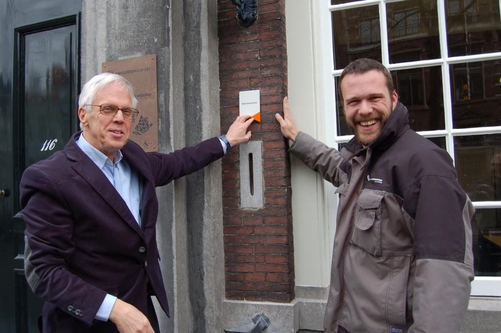 Andries Ponsteen, directeur van het Erfgoedhuis Zuid-Holland en de Monumentenwacht schroefde het exemplaar aan de gevel van het Meisjeshuis in Delft.