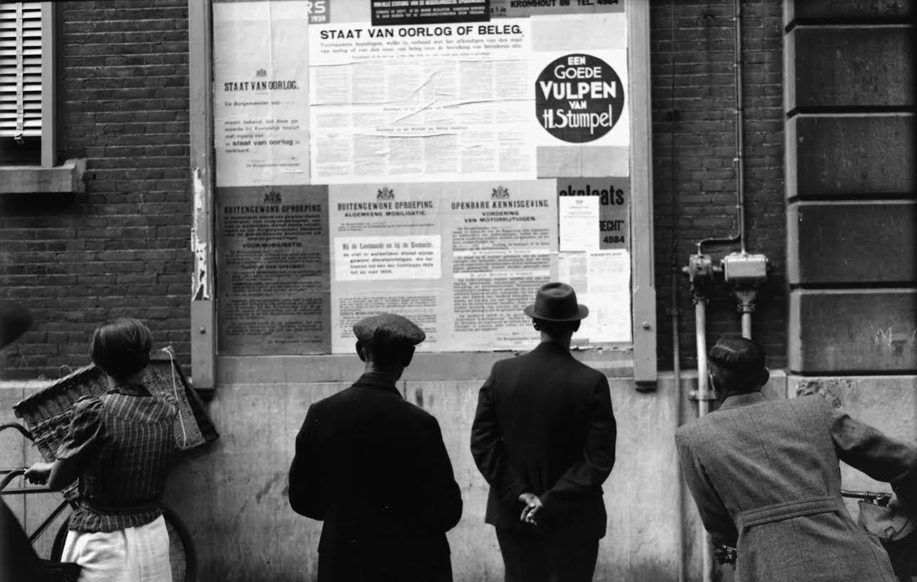 Dordtenaren bekijken de aankondigingen van de staat van oorlog en beleg, de voormobilisatie, de algemene mobilisatie van 28 augustus 1939 en de vordering van motorrijtuigen op het aanplakbord bij het Stadhuis. Foto W. Meijers