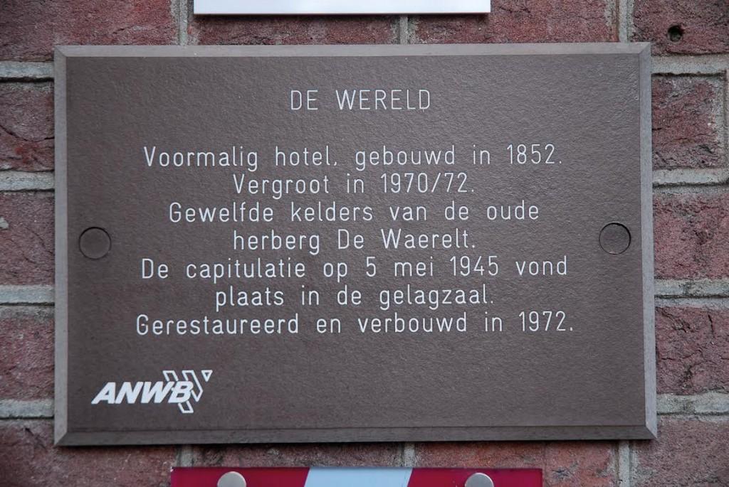 Plaquette aan de muur van hotel 'De Wereld'.