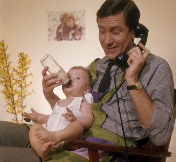 Telefonerende vader met huishoudschort geeft baby de fles. Nederland, [1961]