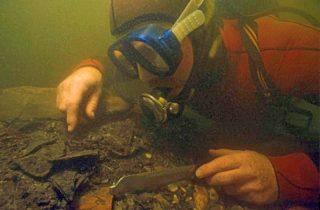 Een onderwaterarcheoloog bovenop de afvalhoop van Ceuclum. Foto: Willem van Kolvoort.