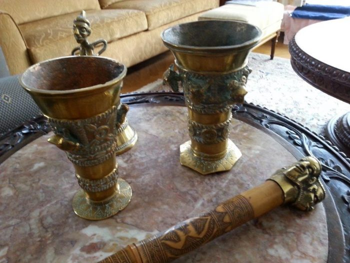 Op de voorgrond de ceremoniële stok van de Sultan van Bamoun en daarachter de twee kelken en de tafelschel
