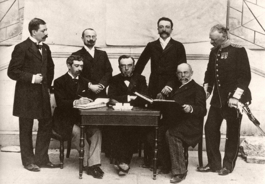 De zeven IC-leden tijdens de Olympische Spelen van 1896 in Athene. V.l.n.r. staand: Gebhardt, Guth-Jarkovsky, Kemeny, Balck. Zittend: De Coubertin, Vikelas en Boulowsky. Bron: De onbekende historie…