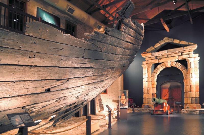 Deel van het achterschip van de echte Batavia en replica van de toegangspoort in de Shipwreck Galleries in Fremantle. (CC BY-SA 4.0 - Vunz)