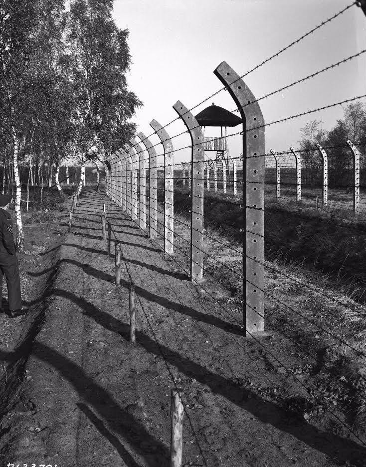 Perspectief-foto prikkeldraadomheining met wachttoren op achtergrond (collectie Canadian Forces Joint Imagery Centre)