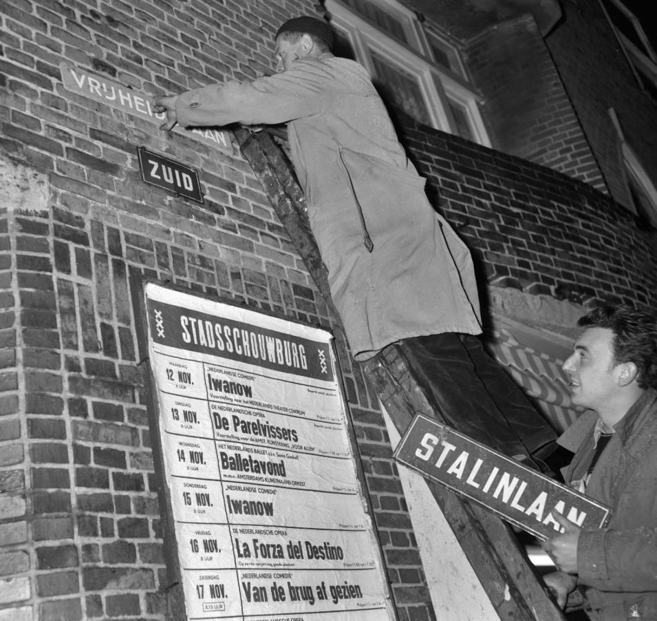 """Een werknemer van de Amsterdamse Dienst van Publieke Werken vervangt in Amsterdam-Zuid de straatnaamplaten met """"Stalinlaan"""" door - voorlopig houten- bordjes met """"Vrijheidslaan"""", na een besluit van de Amsterdamse gemeenteraad, 14 november 1956 (CC0 - Anefo, Herbert Behrens - wiki)"""