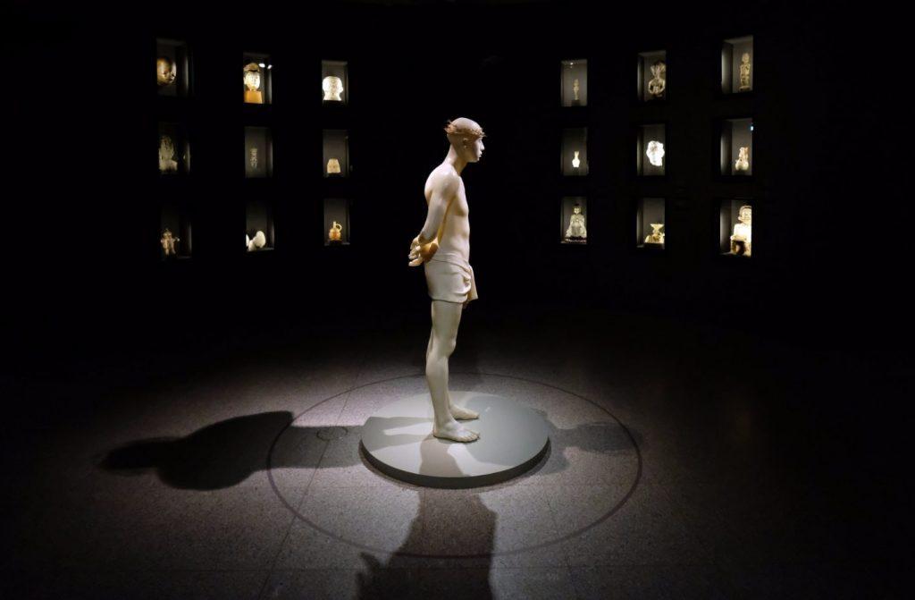Jezus, met doornenkroon maar zonder de vernederingen waarmee hij aan de Joden werd getoond, wordt in de religiezaal omringd door de beelden van 36 goden. - © Kunst- und Ausstellungshalle der Bundesrepublik Deutschland GmbH