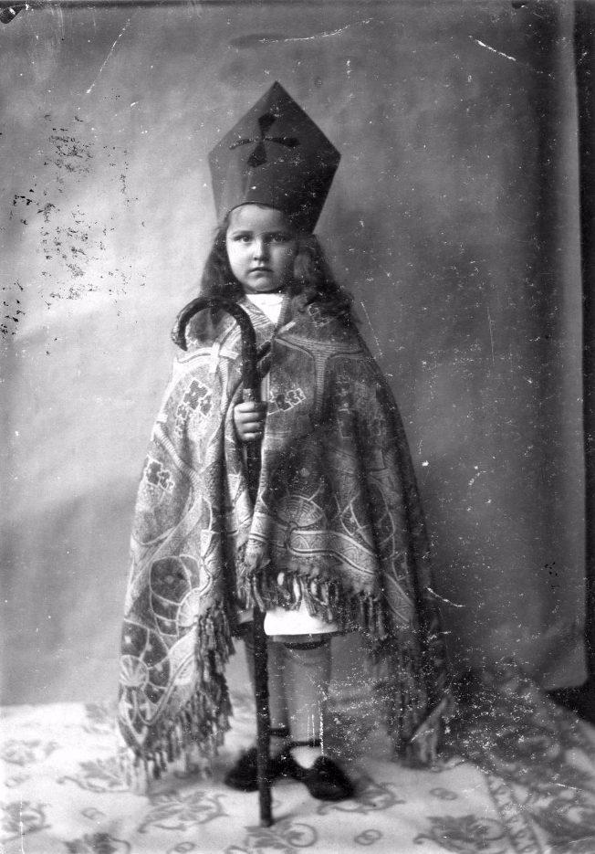 Een meisje verkleed als een jonge Sinterklaas met een zelfgemaakte mijter en een kleed als mantel. De wandelstok [van opa?] dient als staf, 1909. (GVNL, Fotocollectie Het Leven)