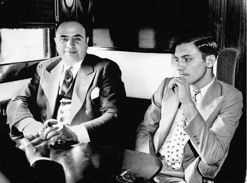 Al Capone in de trein die hem in mei 1932 naar de gevangenis in Atlanta brengt. Hij is zo gaan zitten dat zijn handboeien en de ketting waarmee hij vastzit aan de angstige jonge autodief naast hem, niet zichtbaar zijn. (collectie John Binder)