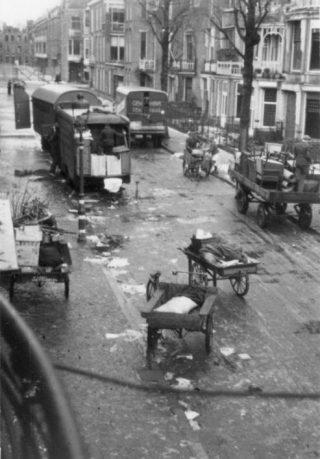 Verhuiswagens en bakfietsen om de evacuatie te realiseren, verzameld in de Nicolaistraat.