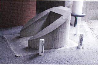 De nooduitgang van de bunker van Economische Zaken lijkt op een afgebroken sokkel, zo ontworpen voor gebruik als het gebouw was ingestort.