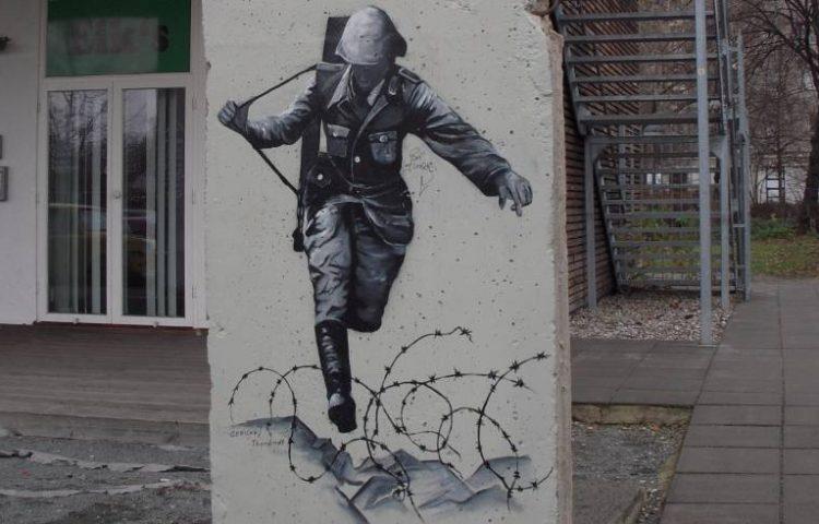 Schilderij naar de foto van Conrad Schumann op een overgebleven deel van de Berlijnse Muur - cc