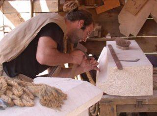 Een steenhouwer neemt een stuk kalksteen onder handen © Guédelon