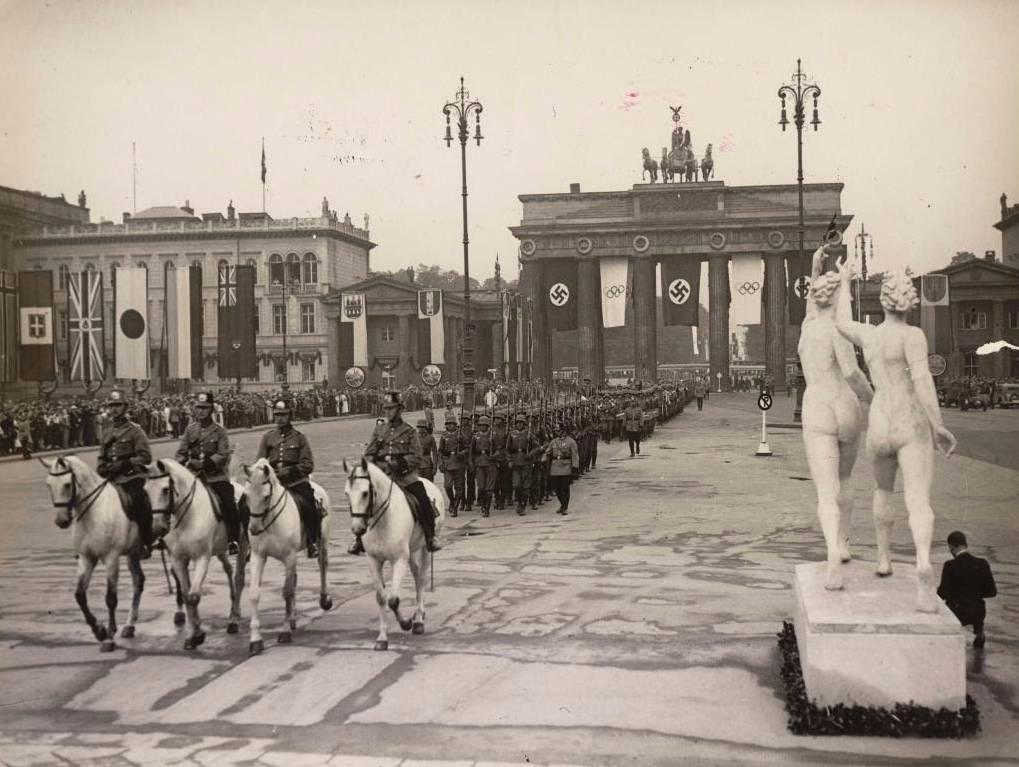 De opening van de Olympische Spelen in 1936, met op de achtergrond de vlaggen van de deelnemende landen. (Bron: Beeldbank WO2, collectie NIOD.)