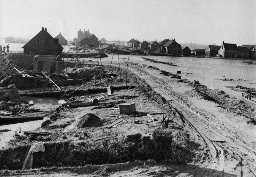 De doorbraak in de Westdijk in Nieuwe-Tonge die overgaat in de Duivenwaardsedijk, met linksachter de Generaal Snijderstraat, en rechts de Duivenwaardseweg. Het hoge pand op de Duivenwaardsedijk is de nu verdwenen cichoreifabriek (Streekarchief GoereeOverflakkee)