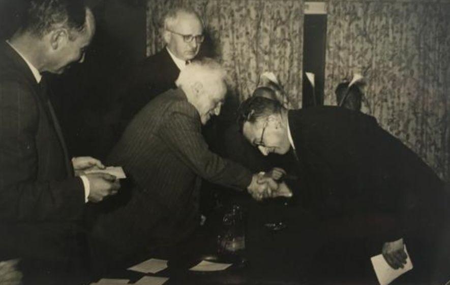 Dr. Menachem Chwojnik buigt voor David Ben-Gurion, de eerste premier van Israël, na het winnen van het schaakkampioenschap van Israël in 1951.