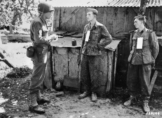 Martin Selling ondervraagt gevangengenomen Duitse ss'ers nabij het front in Frankrijk, 1944. (U.S. Army Signal Corps)