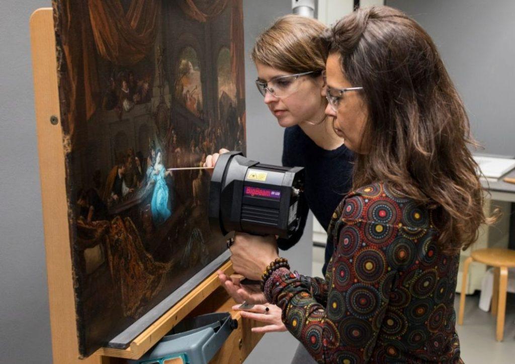 Restauratoren van het Mauritshuis (vlnr) Marya Albrecht en Sabrina Meloni onderzoeken 'De bespotting van Simson' - © Mauritshuis, Den Haag - Fotograaf: Ivo Hoekstra