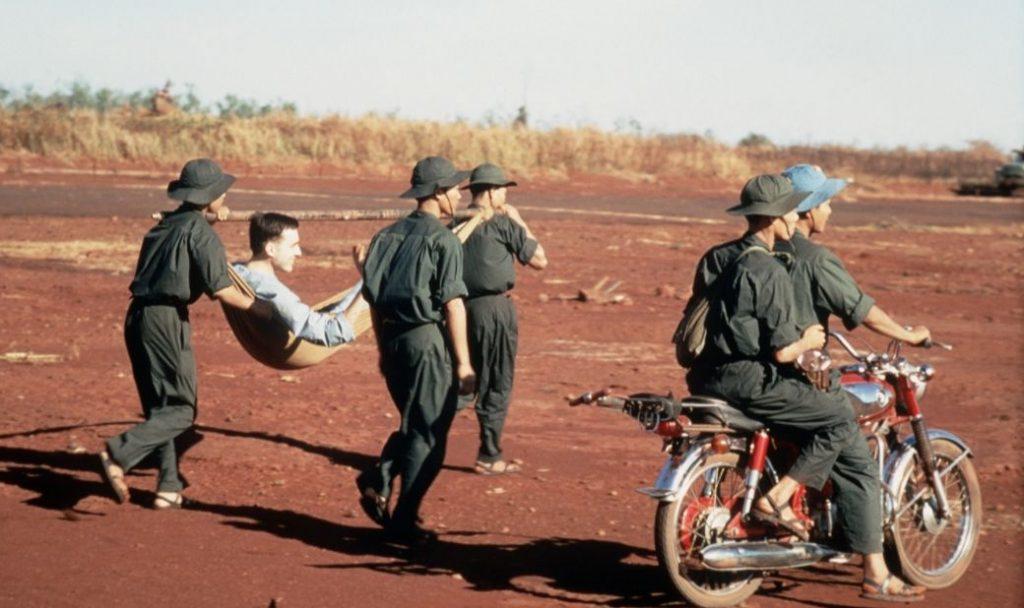 Vietcongsoldaten dragen een doek met een Amerikaanse krijgsgevangene naar een uitwisselingspunt in ruil voor de vrijlating van een aantal Vietcongsoldaten en soldaten van het Noord-Vietnamese leger (1973) - wiki