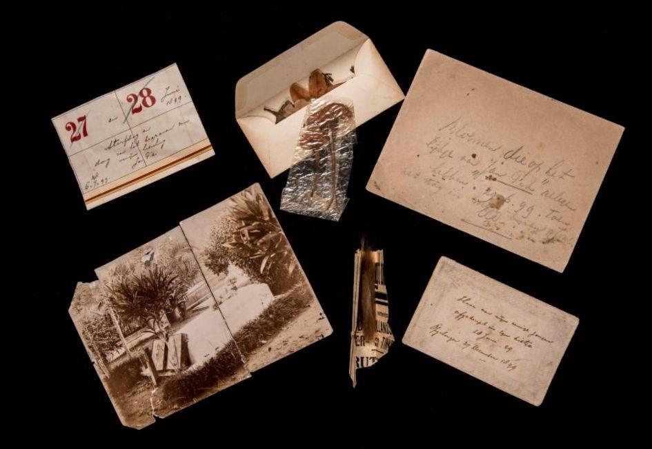 Aantekeningen op een kalender van de overlijdensdatum en het begraven van Norman. bloemen van het graf van Norman, een foto van het graf en de afgeknipte haren van zoon Norman in een krantenknipsel. Foto door Ruben van Vliet