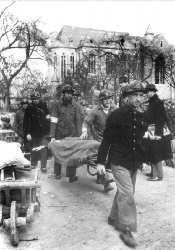 Hulpverleners brengen een slachtoffertje weg uit de vernielde Sint-Vincentiusschool.
