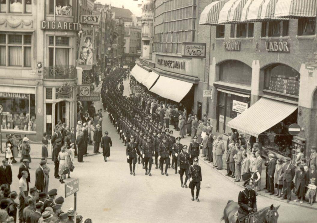 Zwart-witfoto van een mars door de stad van het Politiebataljon Amsterdam, de motordienst en de bereden brigade van het Amsterdamse politiekorps op 2 juli 1941. De foto is gemaakt in de Kalverstraat.
