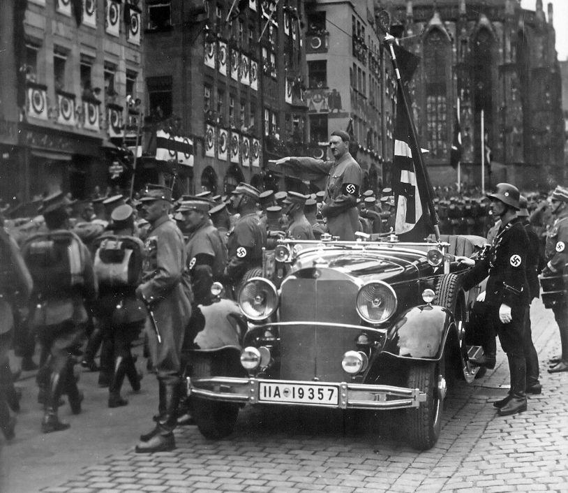 Hitler tijdens een Reichsparteitag in Neurenberg, 1935. Achter hem de Bloedvlag met daarbij Jakob Grimminger (Charles Russell Collection, NARA)