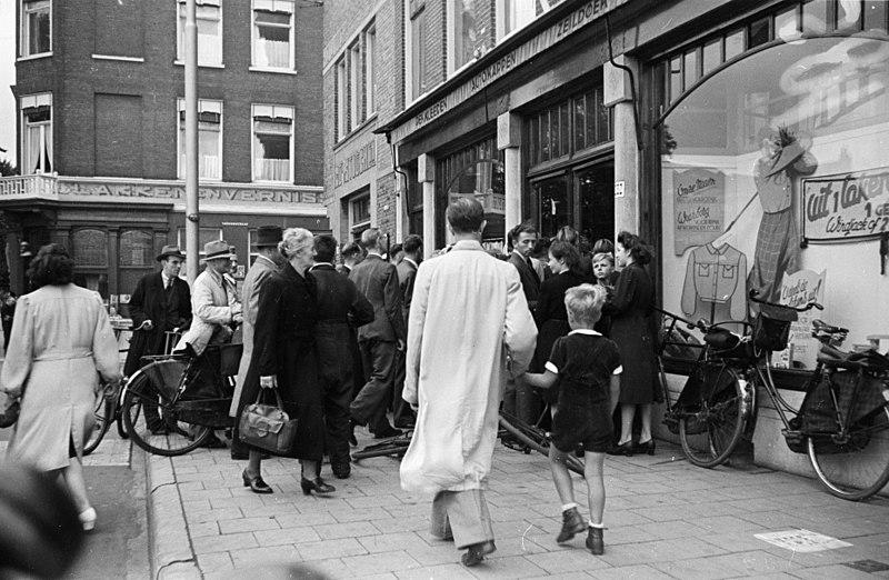 Foto uit de collectie Huizinga van het NIOD. Klanten drommen op Dolle Dinsdag samen bij een winkel, die oranje vlaggetjes verkoopt. Menno Huizinga was onderdeel van de Ondergedoken Camera en maakte illegaal foto's tijdens de bezetting. Dit deed hij hoofdzakelijk in zijn woonplaats Den Haag. (Publiek Domein - Menno Huizinga - NIOD - wiki )