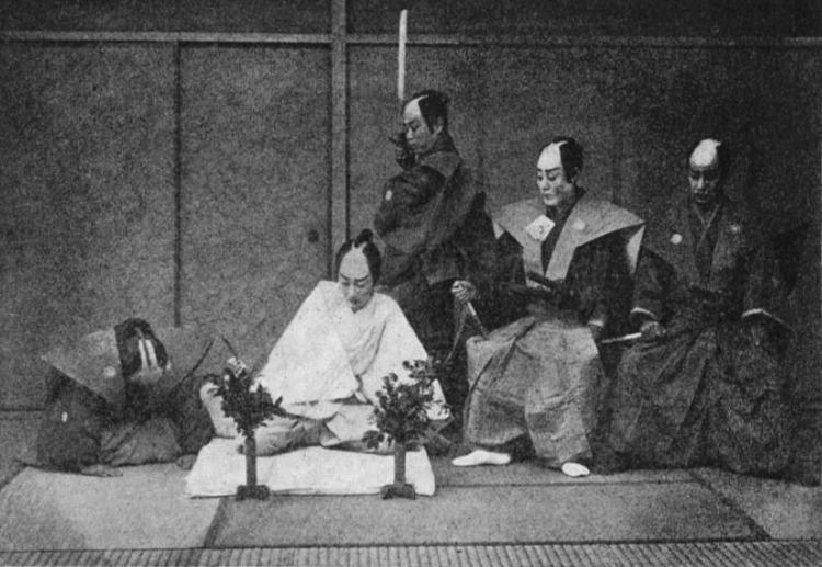 Foto uit 1897 van een in scène gezette Seppukuceremonie. De man in het wit pleegt harakiri / seppuku. (Publiek Domein - wiki)