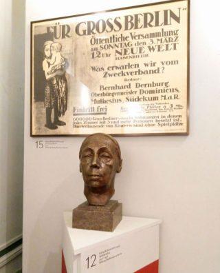 Zelfportret door Käthe Kollwitz uit 1926-1936. Daarboven het affiche uit 1912 voor betere huisvesting in Berlijn. (Foto Kevin Prenger)