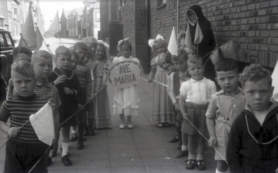 Processie in Grave, kinderen dragen vlaggetjes en houden een koord vast dat aan de bovenkant van het vaandel is vastgehecht. Het meisje in het midden mag het Ave Maria bord dragen. Foto Smeets, Fotostudio Jean Smeets, Grave