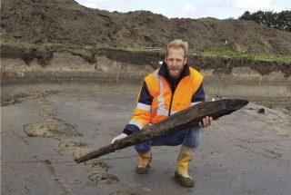 Jeroen Loopik van ADC met een deel van een houten paal van de Romeinse weg  (Foto Provincie Zuid-Holland)