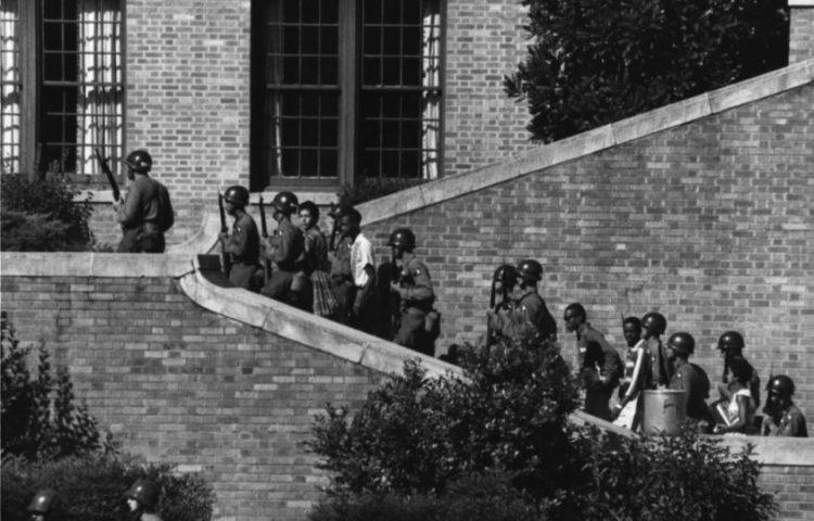 De Little Rock Nine op weg naar school, onder begeleiding van militairen van de 101st Airborne Division (Publiek Domein - US Army)