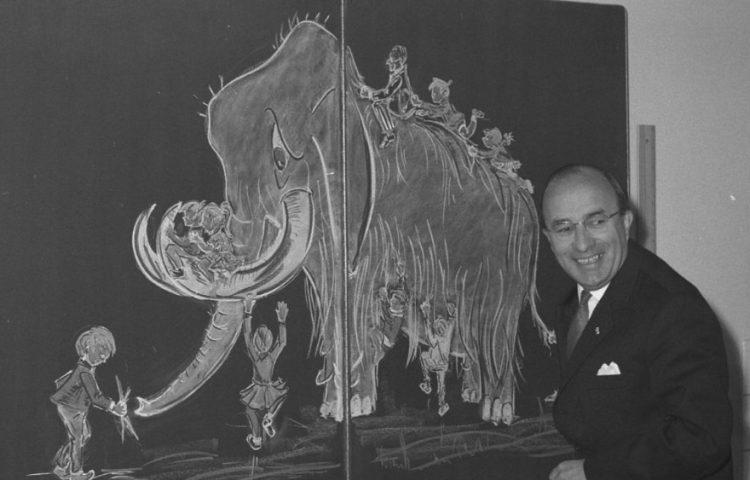 Mammoetwet van 1968 - Minister-president Cals poserend voor een schoolbord waarop een mammoet is getekend (cc0 - Anefo - Voets, Jan, wiki)