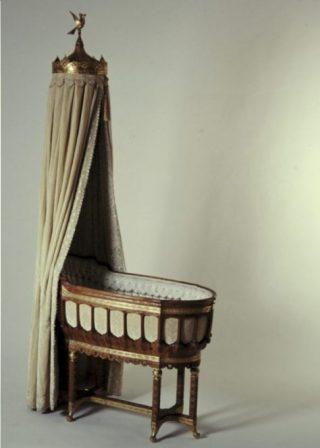 Wieg van Juliana (Koninklijke Verzamelingen) - De wieg met bijbehorend beddengoed werd bij de geboorte van prinses Juliana (1909) aan koningin Wilhelmina geschonken door de vrouwen en meisjes van Amsterdam. Nog altijd in gebruik bij de Oranjes.