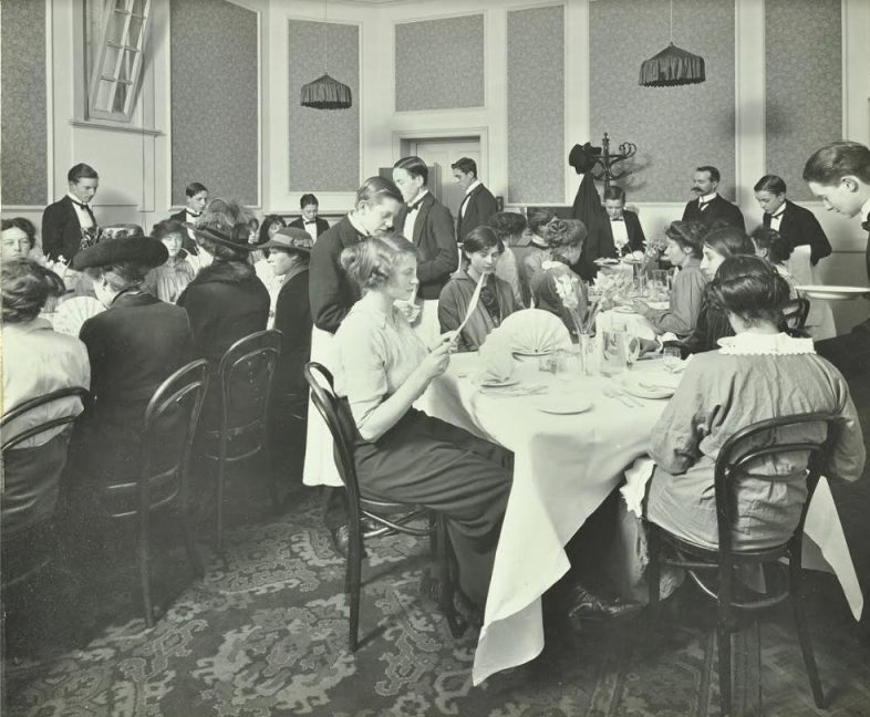 Leerling-koks en -obers serveren een maaltijd in één van de restaurants van de Hotel and Restaurant School. Foto Collectie London Metropolitan Archives.