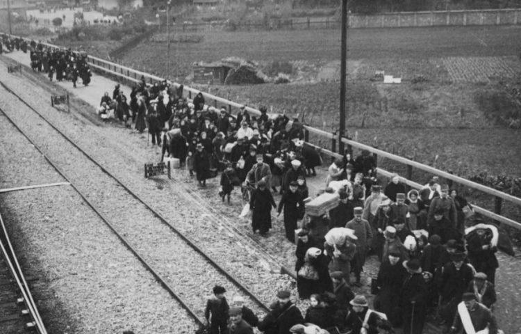 'Franse vluchtelingen lopen begeleid door Nederlandse soldaten richting het N.S. goederenemplacement voor vertrek uit Weert, op de achtergrond het Stationsplein met de tram die de vluchtelingen naar Weert heeft gebracht' (CC BY-SA 3.0 - Gemeentearchief Weert - Europeana)