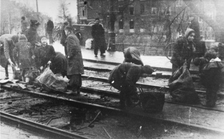 Hongerwinter 1944/1945. Mensen rapen houtblokjes tussen tramrails (CC BY-SA 3.0 - Anefo - wiki)